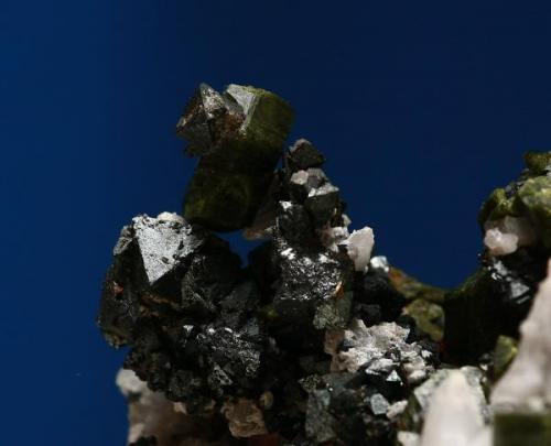 """Cristal de epidota """"tocado"""" por cristal de magnetita. Minas de Cala, Cala, Huelva, Andalucía, España. Tamaño cristal epidota 1,5x0,7x0,5 cm; la magnetita que la """"hiere"""" es de unos 3 mm. (Autor: Inma)"""