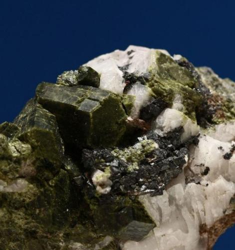 Grupo de epidotas sobre calcita parcialmente disuelta y magnetita. Minas de Cala, Cala, Huelva, Andalucía, España. Tamaño cristal mayor: 1,5x0,8x0,8 cm. (Autor: Inma)