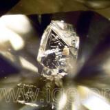 Diamante protogenético incluido en un diamante tallado. Obsérvese las figuras de crecimiento (trígonos) del cristal inclusión. Iluminación de campo oscuro. 40X. (Autor: Egor Gavrilenko)