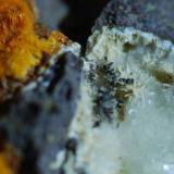 Naranja: ¿Chabasita, Natrolita? Blanco: ¿Todorokita, Natrolita? Imagen de unos 10 mm (Autor: Jose Bello)