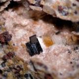 Macla de pseudobrookita, donde el cristal mayor presenta caras estriadas, mientras el cristal menor presenta caras lisas. Campo visual aproximado 4,4 mm. (Autor: Vinoterapia)