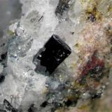 Cristal negro con brillo metálico y caras lisas, nótese la reflexión de la calcita en la parte inferior del cristal de pseudobrookita. Este tipo de cristal suele encontrarse asociado a masas de calcita y hematita. Campo visual aproximado 4,4 mm. Profundidad focal usando Combine ZP, 6 planos. (Autor: Vinoterapia)