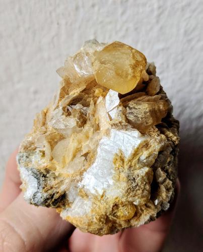 Pieza de Magnesita de cristales lenticulares, bastante rotos y caóticos pero con la gracia de estar adornados por un cristal de Calcita de caras y aristas definidas, brillantes. La Calcita no es uno de los carbonatos más abundantes en este yacimiento.  Pieza colección #2380# (Autor: Carles)