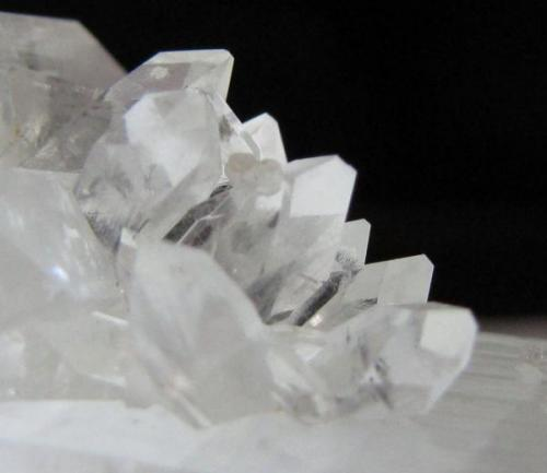 Smaller, sharp and water-clear crystal fluorapophyllites where the smaller crystal meets one of the two main ones.  A little stilbite bowtie is hiding among the points (just above the center of the photo and fuzzy-looking). (Author: Tracy)