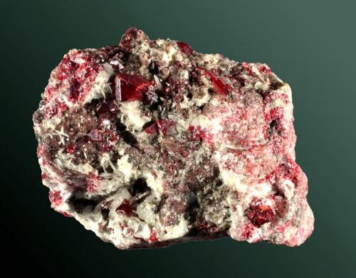 Cinabrio Almadén, Ciudad Real, Castilla-La Mancha. Almadén (m). Cristal equidimensional con predominio del romboedro, con  barita, en matriz (ejemplar de 1995). 4,6 x 3,9 x 4,0 cm. / cristal= 0,6 x 0,5 x 0,4 cm. (Autor: Carles Curto)