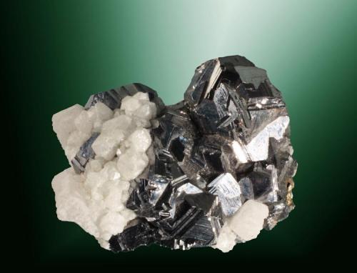 Galena + Calcita Naica, Saucillo (municipio), Chihuahua, México. Agregado de cristales cubo-octaédricos con estrías de crecimiento muy marcadas, en matriz y parcialmente recibiertos por calcita (ejemplar de 1988). 4,6 x 3,7 x 2,2 cm. / cristal pral.: 2,1 x 1,6 x 1,8 cm. (Autor: Carles Curto)