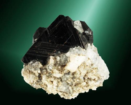 Esfalerita (marmatita) + fluorita Naica, Saucillo (municipio), Chihuahua, México. Cristal maclado, con estrías de crecimiento muy marcadas, en matriz, con cristales octaédricos incoloros de fluorita (ejemplar de 1991). 4,5 x 4,2 x 3,4 cm. / cristal: 3,4 x 2,9 x 2,8 cm. (Autor: Carles Curto)