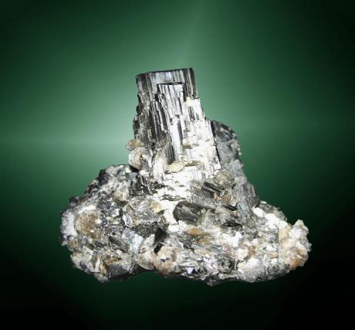 Arsenopirita Panasqueira, Covilha (mun.), Castelo Branco (dist.), Beira Baixa, Portugal.  Agregado paralelo de cristales prismáticos, uno de ellos biterminado, en matriz del mismo mineral y con pequeños agregados hojosos de moscovita (ejemplar de 1982). 6,6 x 5,8 x 4,4 cm. / cristal pral.: 3,0 x 1,7 x 0,8 cm. (Autor: Carles Curto)