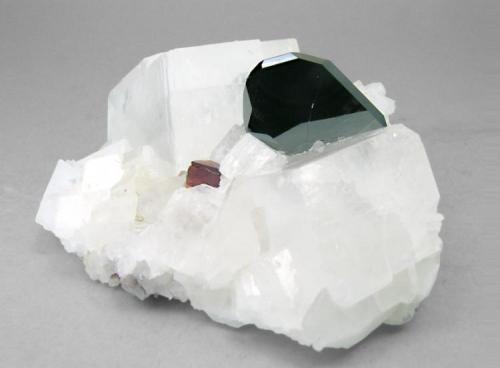 Hematites con Uvita y Magnesita Serra das Éguas, Brumado, Bahia, Brasil Encontrada en 1995 Tamaño de la pieza: 6.4 × 5.1 × 2.4 cm. El cristal más grande mide: 2 × 1.2 cm. Ex colección Silvane Foto: Minerales de Referencia (Autor: Jordi Fabre)