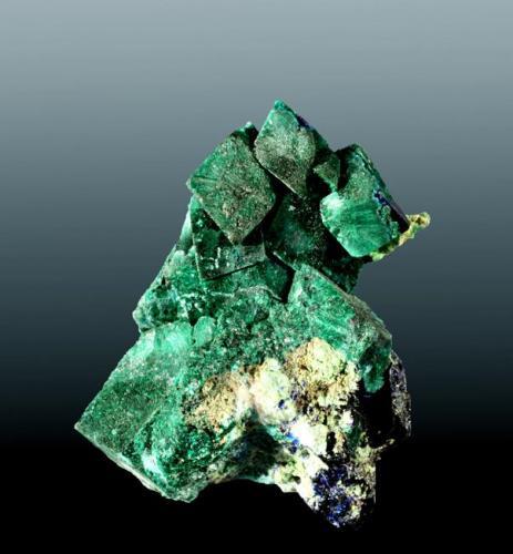 Malaquita psudomórfica de azurita Tsumeb, Otavi (mts.), Tsumeb (constituéncia), Oshikoto (prov.), Namibia. 2,6 x 2,1 x 1,6 cm. (ejemplar) / 0,7 x 0,5 x 0,4 cm. (cristal pral.) Cristales equidimensionales, pseudomórficos de azurita, con cristales de azurita en la base. Ejemplar de 1982 (Autor: Carles Curto)