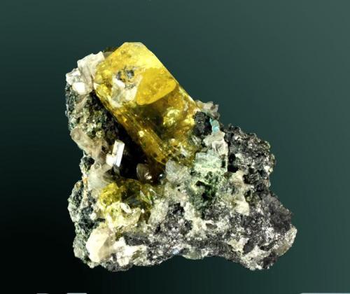 Anglesita + Cerusita Touissit, Oujda-Angad (pref.), L'Oriental (wilaya), Marruecos. Zelidja (m). 5,5 x 5,6 x 2,7 cm. (ejemplar) / 3,7 x 1,6 x 1,6 cm. (cristal pral.) Cristal de color amarillo intenso, con cristales maclados de cerusita, en matriz de galena. Ejemplar de 1990. (Autor: Carles Curto)