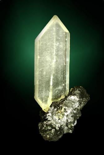 Anglesita Touissit, Oujda-Angad (pref.), L'Oriental (wilaya), Marruecos. Zelidja (m). 4,5 x 2,2 x 1,8 cm. (ejemplar) / 3,7 x 1,3 x 0,5 cm. (cristal) Cristal parcialmente biterminado, inusualmente aplanado y perfilado, con el pinacoide frontal muy desarrollado, en matriz de galena. Ejemplar de 1981. (Autor: Carles Curto)