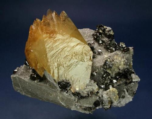 Calcite with Sphalerite on Calcite Elmwood Mine, Middle Tennessee District, Carthage, Smith County, Tennessee, USA 160 x 140 x 117 mm A lustrous, twinned crystal of golden Calcite measuring 107 x 83 x 36 mm is perched on a plate of limestone matrix covered with sparkling, clear scalenahedrons of Calcite. Bright rich-red Sphalerite crystals to 14 mm generously cover the specimen (Author: GneissWare)