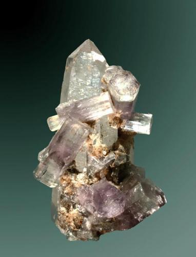 Fluorapatito Panasqueira, Covilha (mun.), Castelo Branco (dist.), Beira Baixa, Portugal. 5,7x3,2x3,0 cm. / 1,4x1,1x1,0 cm. (cristal pral.) Cristales prismáticos violetas, con zonación del color, de mayor intensidad en la zona central del cristals, la mayoría biterminados e implantados en un cristal de cuarzo. Ejemplar de 1984 (Autor: Carles Curto)