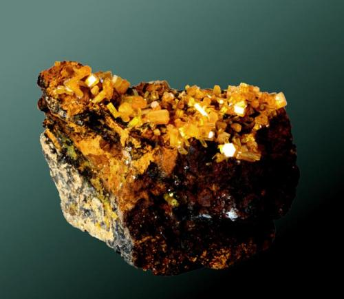 Mimetita Pingtouling, Zhaigang (distr.), Liannan Yao, Guandong, China. Dashuihu (Pingtouling) (m). 7,5x9,2 x 4,1 cm. Cristales prismátics, muchos de ellos biterminados, de color amarillo-naranja, implantados en matriz limonítica. Ejemplar de 2003 (Autor: Carles Curto)
