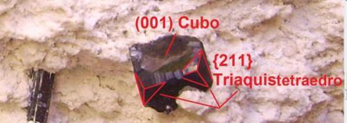 Bixbyíta, pseudobrookita y topacio Thomas Range, Juab Co., Utah, EEUU 8,5 x 4 x 4,5 cm. Indicación de las caras sobre un cubo modificado de bixbyíta. Presenta el cubo (001) y en los vértices, está truncado por tetraquistetraedros {211}. Las aristas del cubo presentan también pequeños truncamientos con estrías no identificados. (Autor: Antonio Alcaide)