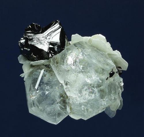 Beryl ( var. Aquamarine ) with Cassiterite Mt. Xuebaoding, Pingwu County,  Mianyang Prefecture, Sichuan Province, China 63.0 x 52.0 x 32.0 mm overall Blocky, highly lustrous, pale-blue Aquamarines to 38 mm are topped by a bright black Cassiterite twin measuring 24 x 22 x 20 mm. White Muscovite crystals to 13 mm provide an accent, as do small untwinned Cassiterite crystals to 5 mm. (Author: GneissWare)