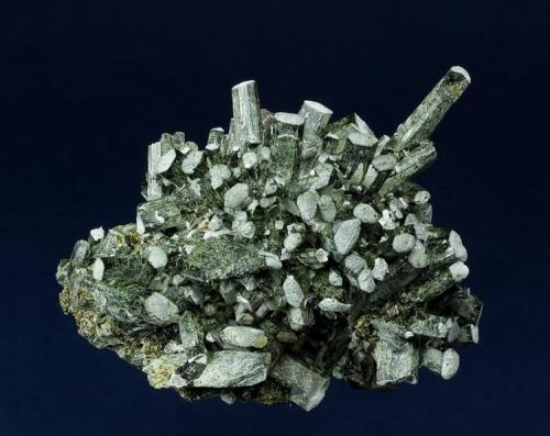 Hedenbergite Huanggangliang Iron Mine, Kèshíkèténg Qí, Chifeng, Inner Mongolia A.R., China 89.0 x 65.0 x 49.0 mm Elongate, semi-lustrous, green tabular crystals of Hedenbergite are arranged in a semi-radiating structure, and are accented with white on the apical termination. Several clear and etched crystals of Calcite to 8 mm are perched on the Hedenbergite. A nice specimen from this prolific locality with no damage. (Author: GneissWare)