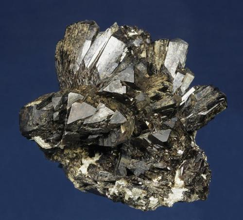 Axinite-(Fe)  Obira Mine, Ono-gun, Oita Prefecture, Kyushu, Japan  60.0 x 52.0 x 43.0 mm  This fine, sculptural specimen from this famous Japanese locality consists of many sharply-terminated, lustrous, clove-brown crystals of Axinite to 21 mm. From the Earl Calvert (1904-1964) collection, this specimen is pristine. (Author: GneissWare)