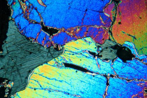Olivino y ortopiroxeno (enstatita) Lanzarote, islas Canarias, España. FOV 3 mm Una vista general de la roca bajo el microscopio. las zonas grises corresponden al ortopiroxeno, las coloreadas al olivino. Fotografía con polarizadores cruzados. (Autor: Vinoterapia)