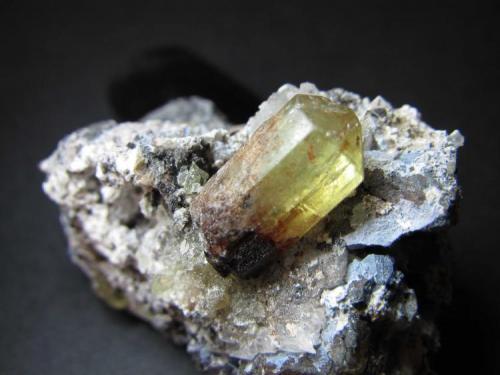 Apatito Cerro de Mercado, Durango, México 1'5 x 0'9 cm. el cristal principal Un cristal oliváceo bien formado (prisma hexagonal terminado en pirámide); otros en la matriz. (Autor: prcantos)