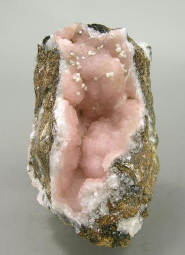 A specimen of Rhodochrosite with very few Kentrolite and minor white crystals of probably Calcite or Aragonite. (Author: Jordi Fabre)