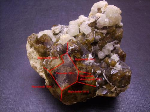 Vesubianita, calcita Fushan Mine, She Co., Handan Prefecture, Hebei Province, China 6 x 6 x 4,5 cm Indicación de las caras. Los cristales, como los que son flotantes del mismo yacimiento, son bipirámides tetragonales con pinacoide como en este caso. Aparece también una sola cara de una pirámide ditetragonal (que de aparecer todas nos daría una bipirámide de ocho caras arriba y ocho abajo en lugar de cuatro y cuatro como en este caso). Tengo un cristal flotante en el que el pinacoide aparece sólo rematando una pirámide, por abajo la terminación es en punta. (Autor: Antonio Alcaide)