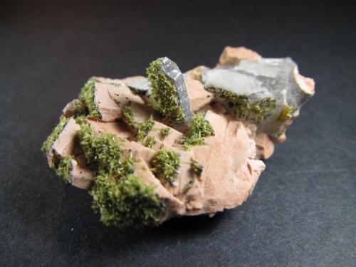 Epidota, cuarzo ahumado y feldespato Luoyang, Henan, China 4 x 3'5 cm. Un cristal de cuarzo ahumado sobre feldespato (probablemente ortosa) con un recubrimiento de pequeños cristales de epidota. (Autor: prcantos)