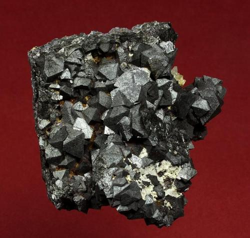 Magnetite Hercules Mine, Municipio de Camargo, Chihuahua, Mexico 67 x 62 x 40 mm  Shiny black, octahedral crystals of Magnetite to 12 mm are intergrown and accented by a cluster of small, clear Quartz crystals. In excellent conditon, this specimen was self collected during the 1993 Grossular collecting trip Graham and I took. The outcrop lies just outside the mine, and was pointed out to us by Felix who was a mining engineer at the Hercules mine, following some exploratory blasting. (Author: GneissWare)