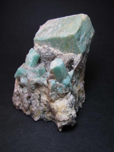 Microclina (variedad amazonita) Crystal Peak area, Teller County, Colorado, Estados Unidos 7 x 7 x 8 cm. Esta pieza también me gusta especialmente porque aparecen los cristales en su matriz, en este caso una pegmatita.  Hay un cristal enorme de 26 x 29 x 42 mm., de buen color y casi flotante pero mal rematado.  Debajo de él se ven dos cristales medianos de 1'5 cm. de forma más perfecta, junto a otros cristales menores. (Autor: prcantos)
