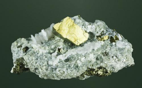 Calcopirita Mina Xianghualing, Xianghualing, Linwu, Chenzhou (pref.), Hunan (prov.), China. 3,9x7,5x4,8cm. (cristal: 2,8x1,7x1,6cm.) Cristall diesfenoidal con crecimientos paralelos de pequeños cristales lenticulares de calcita, en matriz. (Autor: Carles Curto)