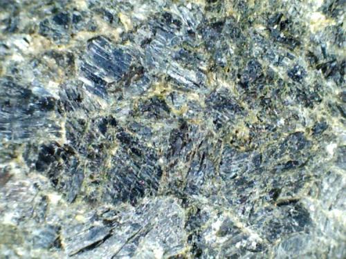 Hornblendita de granate (detalle) Barton Garnet Mines, Gore Mountain, Nueva York, Estados Unidos 30X Detalle de los cristales tabulares de hornblenda que forman la matriz de la roca.  En algún caso se aprecia lo que parece el sistema típico de exfoliación del anfíbol (centro izquierda de la foto). (Autor: prcantos)