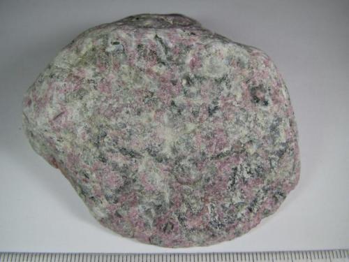 Naujaita Complejo de Illimaussaq, Fiordo Kangerdlussaq, Julianebab District, Sur de Groenlandia 7 x 6.5 cm. Variedad agpaítica de una sienita de nefelina y sodalita, caracterizada por una textura poiquilítica con prequeños cristales de sodalita (granos grises) incluidos en granos más grandes de feldespato alcalino, arfvedsonita, aegirina (negras) y eudialita (mineral rosa).  La sodalita da intensa fluorescencia de color naranja con luz ultravioleta. (Autor: prcantos)