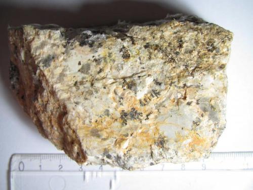 Granito (vista anterior) Streuberg, Bergen, Vogtland, Sajonia, Alemania 10 x 4 cm. (x 3'5 cm. de grosor) Roca de grano grueso, muy rica en grandes feldespatos blancos y algunos cristales grises de cuarzo.  Se aprencian algunas formaciones dendríticas de óxidos de manganeso. (Autor: prcantos)