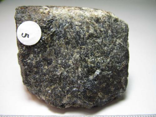 Gabro Localidad desconocida 4 x 3'5 cm. Gabro de una colección didáctica (sin localidad), de grano grueso (los cristales se distinguen como zonas con más brillo).  Se distinguen granos verdosos (seguramente de olivino) en la masa oscura. (Autor: prcantos)