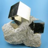 Four undamaged cubic pyrite crystals with mirror-like faces intergrown on a matrix of marlstone (some people claim it to actually be limolite). Field collected in spring 2007. (Author: Carles Millan)