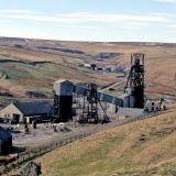 Frazer's Hush was a modern mine, operating between 1974 - 1999. It was located at the far northwest end of Rookhopeburn, just beyond the Groverake Mine. The workings can be seen in the middle background of the photo, just left of the main Groverake head frame. The Frazer's Hush workings were declines rather than shafts, so no head frames were erected on site. The mine is best known for a find of high quality purple fluorites that happened in 1987-1988. The photo was taken in 1999 shortly after the closure of both mines. The sites have largely been cleared since, and the only thing that now remains is the main Groverake head frame. (Author: Jesse Fisher)
