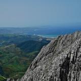 Vista al oeste desde la cima con el puerto de Tanger Med en el centro y el Cabo Espartel al fondo.  La estratificación, aquí en posición vertical, es entre decimétrica y métrica. (Autor: Josele)