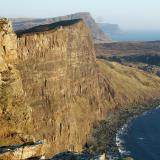 Cliff-top above Oisgill Bay, Isle of Skye. March 2007.Tertiary basalt lava flows are easily seen in the 600' (200m) vertical sea-cliff. The even bigger cliff-top in the middle distance is called Waterstein Head (nearly 1000' high or 270m) and tucked in behind it is Moonen Bay. (Author: Mike Wood)