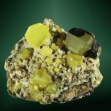 Azufre Novafeltria, Pesaro-Urbino, Marche, Italia. Perticara (m). Cristales equidimensionales parcialmente recubiertos por betún, en matriz bituminosa. 3,7 x 4,5 x 3,9 cm. (Autor: Carles Curto)