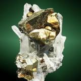 Calcopirita Huarón, Cerro de Pasco, Pasco, Perú. Alimón (m). Cristal pseudotetraédrico maclado, en cuarzo (cristal de roca), con pirita (ejemplar de 1984). 5,6 x 4,3 x 4,1 cm. cristal pral.= 3,0 x 2,7 x 2,3 cm. (Autor: Carles Curto)