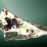 Cinabrio Tongren, Tongren (pref.), Guizhou (Kweichow), China. Yanwuping (m). Grupo de cristales, uno de ellos dominante, con el romboedro agudo dominante, maclados, implantados en dolomita blanca, en matriz (ejemplar de 1990). 4,9 x 7,2 x 3,7 cm. / cristal pral.= 1,2 x 1,1 x 1,2 cm. (Autor: Carles Curto)