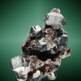 Galena + cuarzo + esfalerita     Chaojia, Rucheng (dist.), Chenzhou, Hunan, China. Rucheng (m). Cristales cubo-octaédricos maclados (macla según la ley de la espinela), en matriz de esfalerita acaramelada roja, parcialmente recubierta de microcristales de cuarzo (ejemplar de 2010). 8,0 x 5,2 x 4,1 cm. / cristal pral.: 2,4 x 1,4 x 1,4 cm. (Autor: Carles Curto)