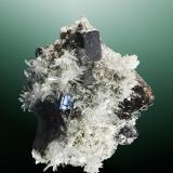 Galena + cuarzo + esfalerita Huarón, Cerro de Pasco, Pasco (dept.), Perú. Alimón (m). Cristal cúbico ligeramente elongado, implantado en una drusa de cristales de cuarzo (c.de roca), con esfalerita (ejemplar de 1984, recolectado entre verano de 1983 y verano de 1984). 8,6 x 5,9 x 5,0 cm. / cristal: 1,3 x 1,1 x 1,1 cm.            recol•lecció: 1983 - 1984            notes: Viatge al Perú de J.Barba el 1984. (Autor: Carles Curto)