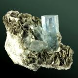 Berilo (aguamarina) + moscovita Nagar (Nagir), Hunza (Baltit) (valle). Gilgit, Area Nord, Pakistan. Fiqhar (Fighar). Cristal prismático transparente, de color azul uniforme, con moscovita, en matriz. (ejemplar de 1993). 6,4 x 6,2 x 2,9 cm. / cristal: 3,0 x 1,3 x 1,5 cm. (Autor: Carles Curto)
