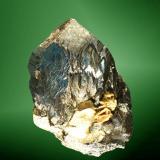 Arsenopirita Panasqueira, Covilha (mun.), Castelo Branco (dist.), Beira Baixa, Portugal. Cristal prismático, con curvaturas, con un pequeño agregado hojoso de moscovita (ejemplar de 1989). 2,6 x 2,7 x 2,6 cm. / cristal pral.: 2,8 x 2,1 x 1,7 cm. (Autor: Carles Curto)