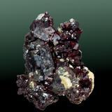 Cuprita Rosemont, Helvetia-Rosemont (dist.), Santa Rita (mts). Pima Co., Arizona, EUA. Helvetia (m). 4,7 x 4,3 x 1,5 cm. / cristal pral.= 1,6 x 1,1 x 0,6 cm. Agregado de cristales formados por el cubo y el rombododecaedro, translúcidos y en matriz. Ejemplar obtenido en 1975. (Autor: Carles Curto)