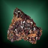 Cuprita + Cobre Linkinhorne, Liskeard (dist.), Cornwall, Inglaterra, Reino Unido. Ejemplar obtenido en 1966. 3,6 x 3,5 x 0,5 cm. / cristall pral.= 0,3 x 0,3 x 0,2 cm. Cristales cúbicos, algunos de ellos alargados y deformados, sobre cobre nativo. (Autor: Carles Curto)