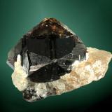 Casiterita Amo, Ximeng Wa, Simao (pref.), Yunnan (prov.), China. Amo Sn (m). 4,0 x 2,8 x 2,5 cm. (ejemplar) / 3,2 x 2,7 x 2,5 cm. (cristal) Cristal equidimensional maclado, negruzco con áreas muy transparentes, en matriz de cuarzo. Ejemplar de 2006 (Autor: Carles Curto)