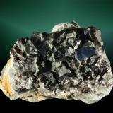 Casiterita Cínovec (Zinnwald), Ústecký (Ústí nad Labem) (dist.), Ústecký (Ústí nad Labem) (región), República Checa. 6,4 x 4,7 x 4,8 cm. (ejemplar) / 1,3 x 1,0 x 0,8 cm. (cristal pral.) Cristales prismáticos maclados, en matriz. Ejemplar de 1968 (Autor: Carles Curto)